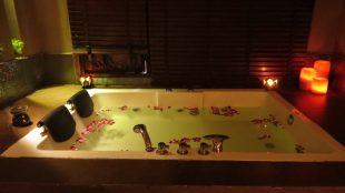 Sensual candlelit Jacuzzi with rose petals floating around